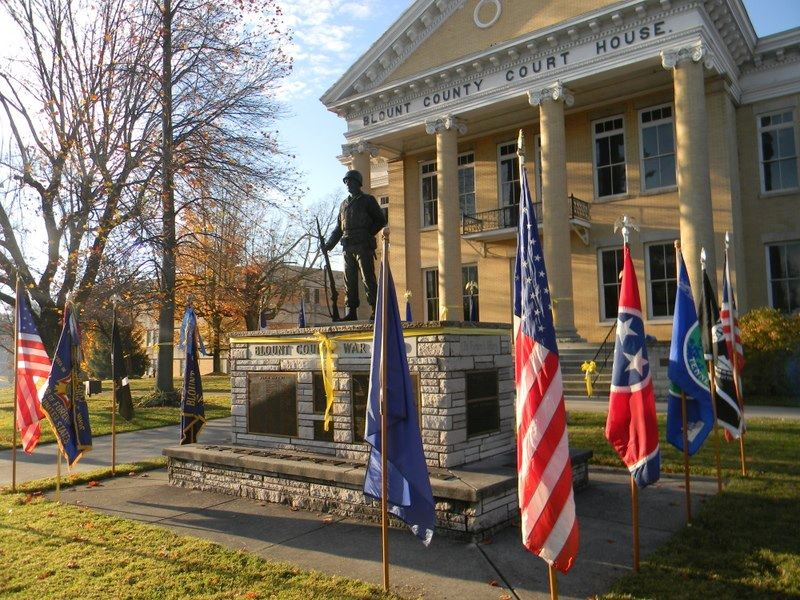 Image of Blount County War Dead memorial, wrapped in yellow ribbon, with flags on perimeter